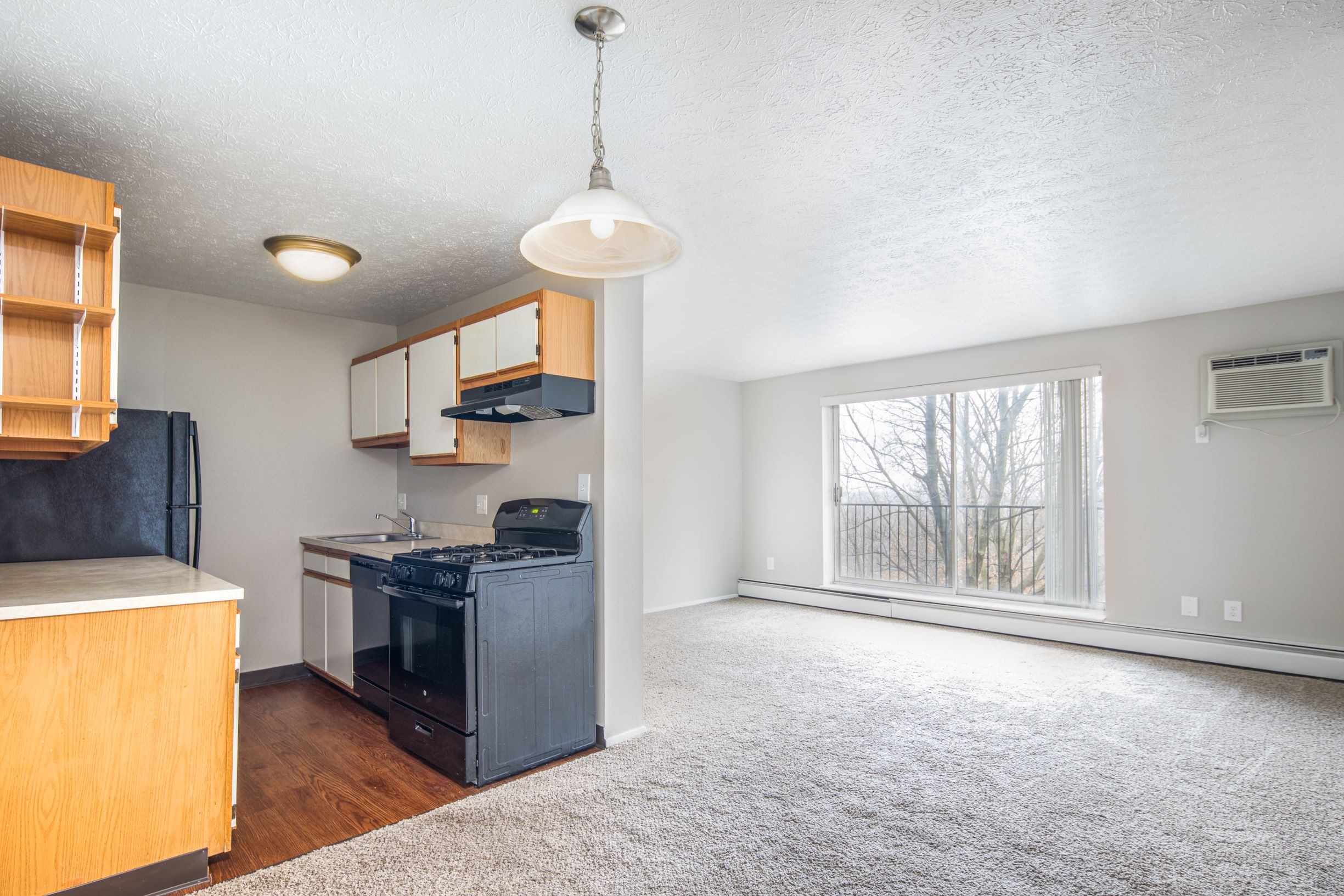 Kitchen leading into living room with large bright windows